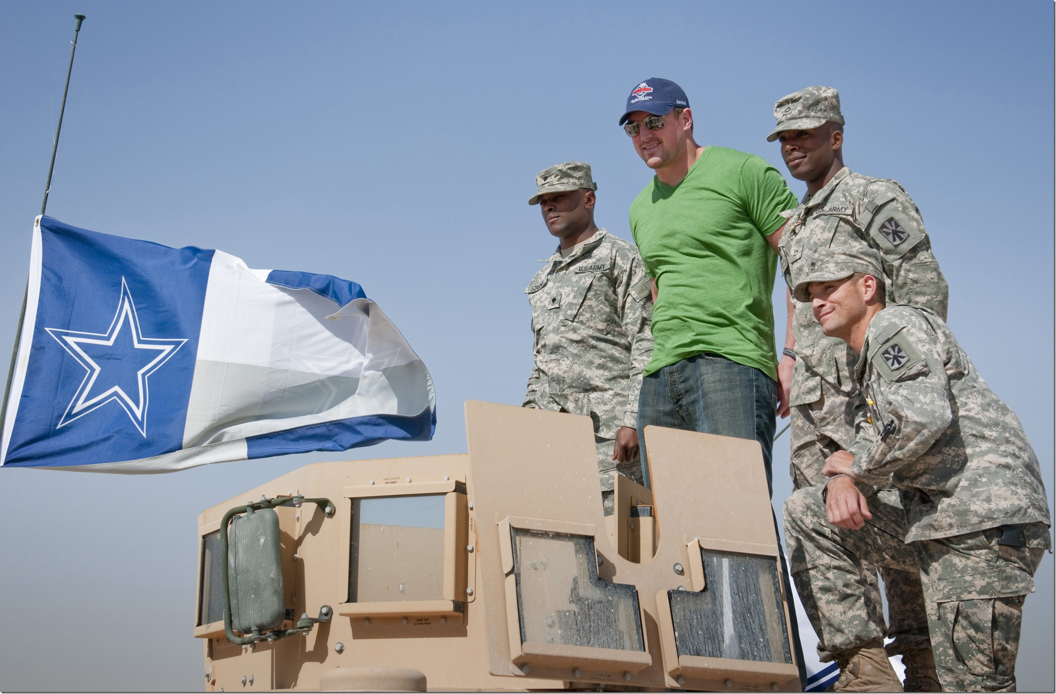 NFL player Jason Witten-Dallas Cowboys poses for a photo with Cowboys fans on top of a Humvee proudly displaying a Cowboys flag, which Witten later autographed.