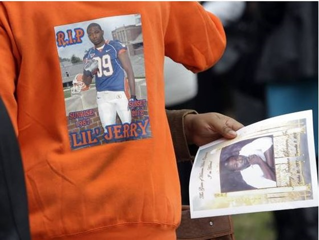 A man wears a shirt picturing Jerry Brown Jr. as another holds a program for Brown's funeral service outside Hopewell Missionary Baptist Church Saturday in St. Louis - The Boys Are Back blog