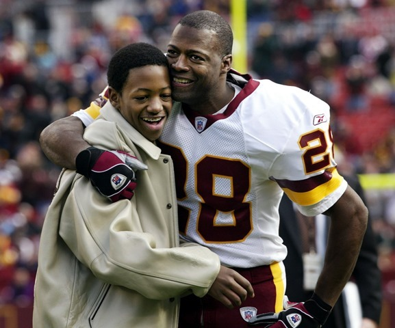 Washington Redskin Hall of Famer Darrell Green hugs his son, Jared, 13, during a ceremony before his last game in 2002 - The Boys Are Back blog 2013